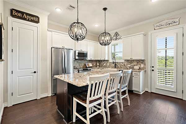 Photo #10 Gourmet kitchen with Level 5 granite counters and backsplash; extended island with room for seating. All electric stainless steel appliances. Pantry closet. Upgraded farmhouse sink and faucet. Iron cage chandeliers.