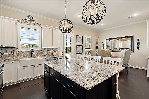 Photo #11 Gourmet kitchen with Level 5 granite counters and backsplash; extended island with room for seating. All electric stainless steel appliances. Pantry closet. Upgraded farmhouse sink and faucet. Iron cage chandeliers.