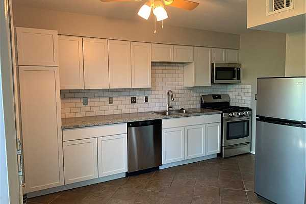 Photo #8 New cabinets, pantry, granite countertops and microwave in open tiled kitchen