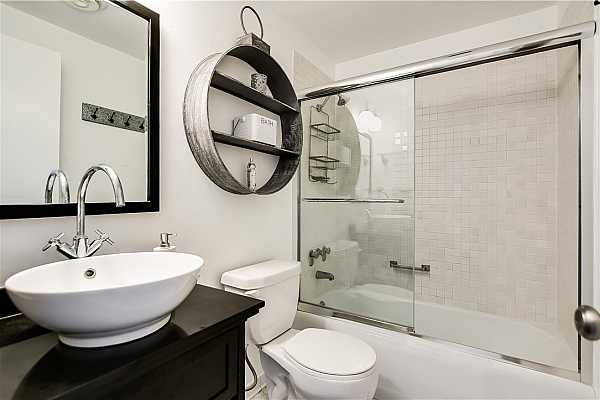 Photo #15 Nice size for guest bathroom.  Tub/shower combination with glass doors.