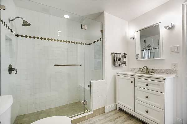 Photo #21 Good size master bath with glassed in walkin shower.  Shower has bench seating.  Sconces on the wall helps with lighting.