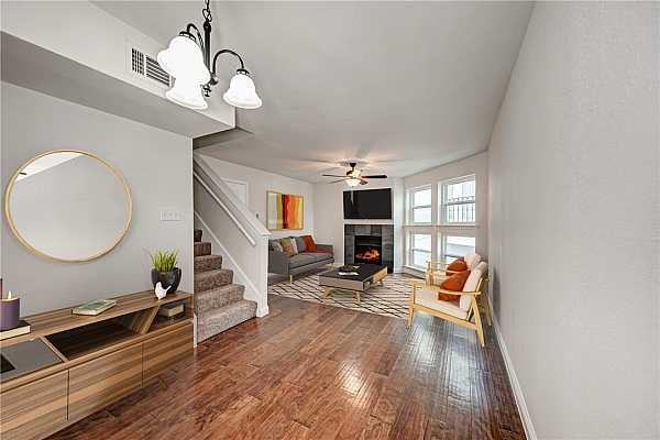 Photo #1 High ceilings, wood flooring, and a welcoming wood burning fireplace in the cozy family room of 1500 Woodlawn Boulevard #11!
