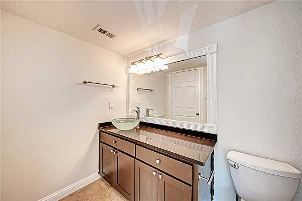 Photo #11 This full bathroom is illuminated by the shimmering light fixture!