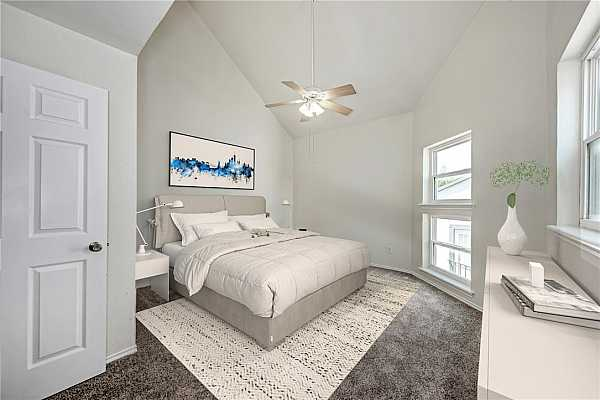 Photo #13 The spacious primary bedroom features high ceilings, a ceiling fan, and carpet flooring throughout.