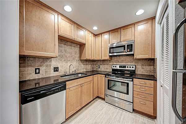Photo #4 Graceful granite countertops and elegant lighting throughout the well-lit kitchen.