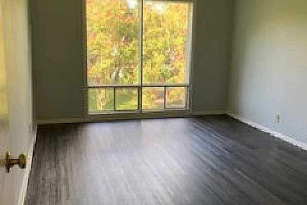 Photo #3 Bedroom also has large window looking out over lush greenery