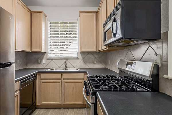 Photo #11 The small kitchen features some stainless steel appliances: a gas range, built-in microwave, and fridge.