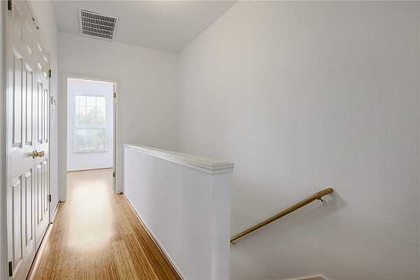 Photo #14 Upstairs hallway separating the two bedrooms. Laundry closet doors are visible on the left.