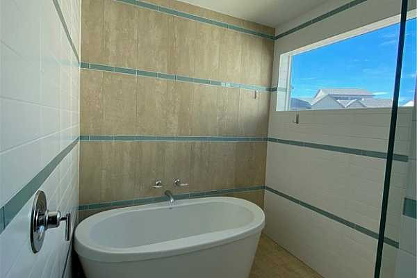 Photo #17 A wonderful master spa bath with soaking tub, shower and window letting in natural light.