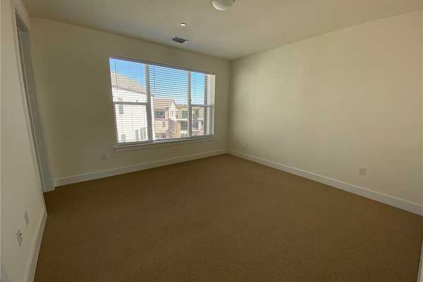 Photo #24 3rd level bedroom with attached full bath and walk-in closet. Large windows for natural light.