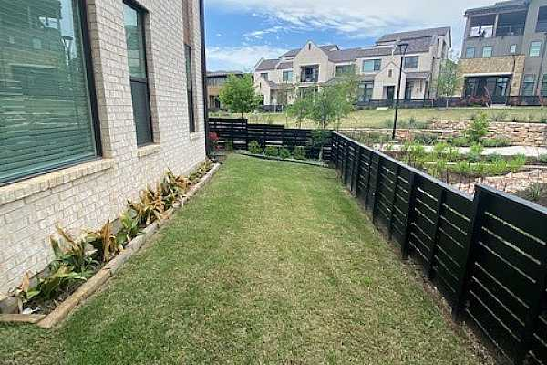 Photo #7 Landscaped side yard with grass & back gate for outside access to garage & driveway.