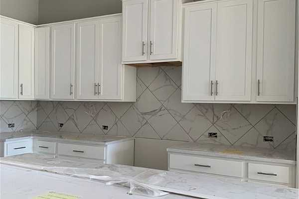 Photo #2 Kitchen feaures white cabinetry and quartz countertops.