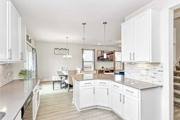 """Photo #9 Cook delicious meals in the gourmet kitchen complete with crisp white 42"""" cabinetry with stainless-steel hardware, a timeliness glass backsplash, and sleek quartz countertops."""