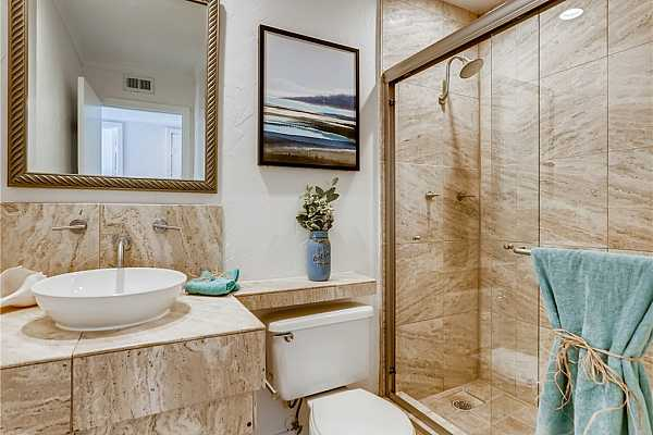 Photo #14 THE PRIMARY BATH ALSO HAS TRAVERTINE TILE FLOORS, COUNTERTOPS AND SHOWER AS WELL AS A NEW SINK, SHOWER DOOR AND SHOWER FIXTURE.  THERE IS ALSO A LINEN CLOSET.