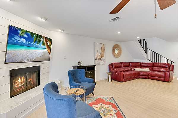 Photo #4 Welcome to the Great Room Living with warming wood burning corner fireplace surrounded in shiplap and mounted overhead, a new television