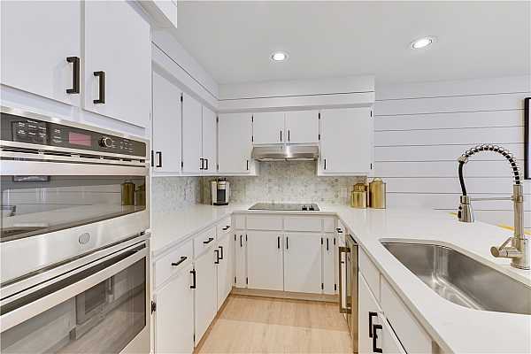 Photo #8 Stylish Galley-Style Kitchen with new countertops, new backsplash, new faucet, new SS wall appliances, new pulls