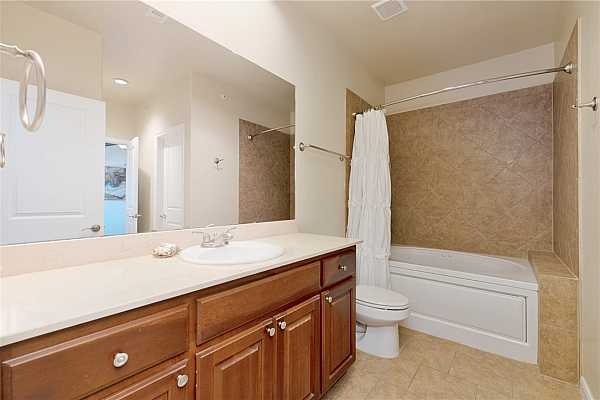 Photo #19 The guest bathroom features a large single vanity, ample storage space, and a deep soaking tub.
