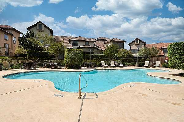 Photo #25 The community pool has many lounge chairs and outdoor dining tables for residents and their guests.