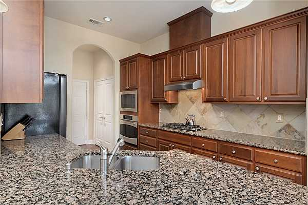 Photo #6 The kitchen offers an abundance of cabinetry for storage topped with sleek granite countertops.