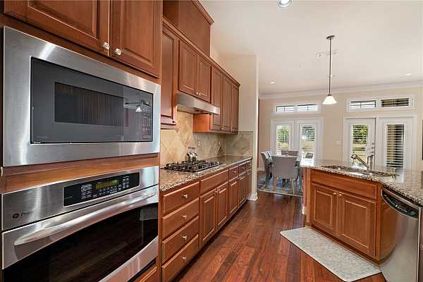 Photo #7 The kitchen is equipped with high-end stainless-steel appliances including a built-in oven and a gas cooktop with a range hood.