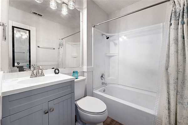 Photo #19  Full bath has new vanity with sink, faucet, lights, toilet and bead board wall accent