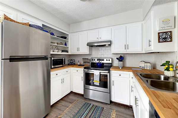 Photo #9 Cute galley kitchen has been totally updated with new appliances, subway tile back splash, sink & faucet.  New flooring too! Fridge does not convey.