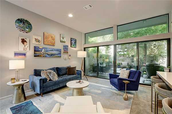 Photo #4 Open living space with soaring ceilings and a wall of windows bring the outdoors in
