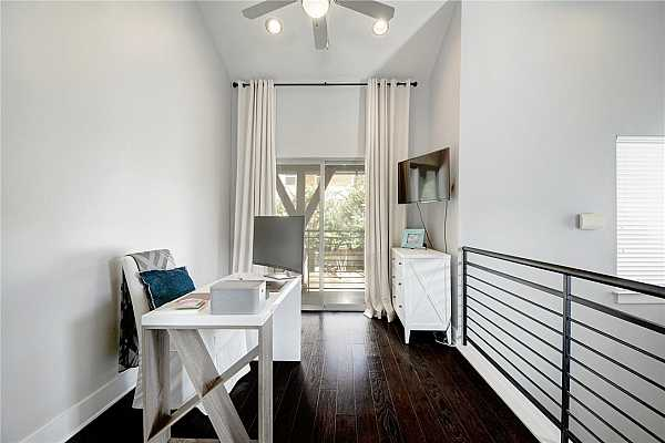 Photo #16 This amazing bonus square footage makes for a great office, yoga studio or work out area.  Notice the new iron railings that are consistent with exterior railing designs (clever).  Wood floors, custom drapes and a sliding balcony door for tree top views.