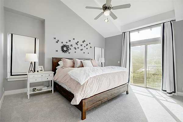 Photo #19 Sweet dreams await in this luxurious master suite with hill country views, soft neutral paint, soaring ceilings, light carpeting in perfect condition, custom lined draperies with blackout features.