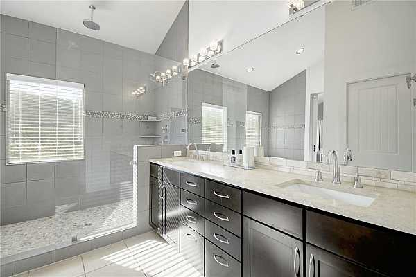 Photo #22 Upgraded, updated and simply fabulous primary bath retreat.  Double vanity sinks, high end stone counters, chrome hardware, upgraded lighting, paint, walk in glass shower with tile and river rock flooring.  Walk in closet behind you with barn door slider.