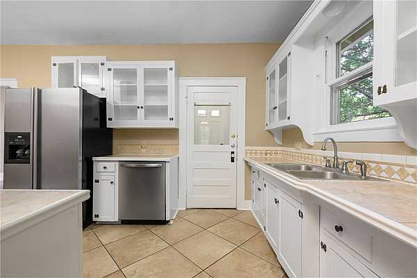 Photo #10 Kitchen with formal dining to the right and 2nd laundry area and back door leading to a porch to the left.