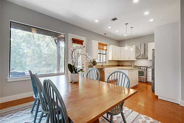 Photo #12 A large picture window in the dining room captures the lush treetop views