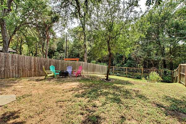 Photo #32 The backyard is fully fenced with a wood privacy fence that separates the neighbors yard and a mesh fence at the rear of the property so you can enjoy unobstructed views of the trees just beyond