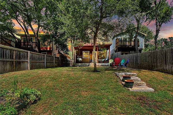 Photo #5 The delightful backyard will be one of your favorite places to spend time with lovely landscaping and nothing but the views of lush trees at the back of the property