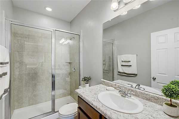 Photo #15 The soothing primary bathroom is very spacious. There is a large vanity with chrome faucets. The tile walk-in, over-sized shower gives this bathroom a great touch.