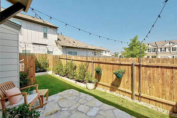 Photo #23 Stepping out in to this adorable backyard, you are welcomed with a large, stone patio, nicely done landscaping with stone planters with fresh mulch. It is a great spot for enjoying the backyard.