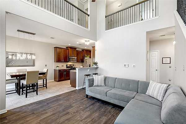 Photo #4 Welcome into this beautiful, open concept home! Notice the soaring ceiling in the large, open living room with beautiful hand scraped, wood-looking vinyl plank flooring that was just installed in September 2021. It is very durable and is more water, pet, etc., resistant.