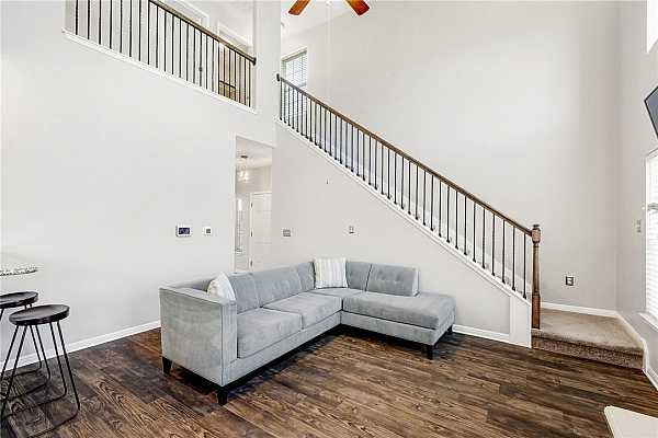 Photo #6 The living room is a great size. The wood balusters and iron spindles are a great touch and give this space character.