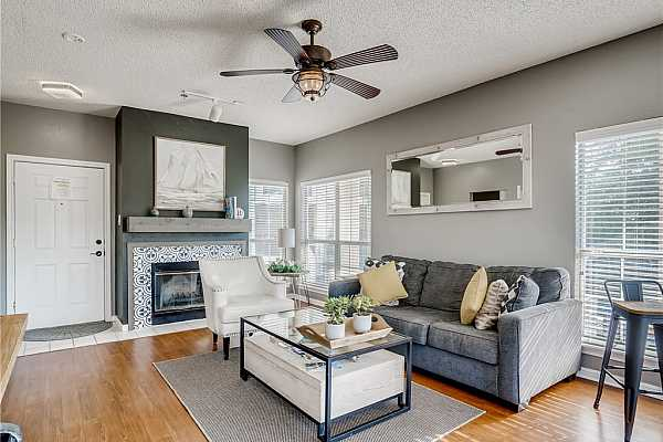 Photo #5 Furnished living room with large windows, fireplace, and wood laminate floors, and updated fixtures.