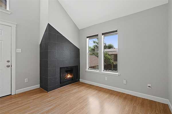Photo #3 Front living room with lovely natural light, vaulted ceilings, and a cozy fireplace.