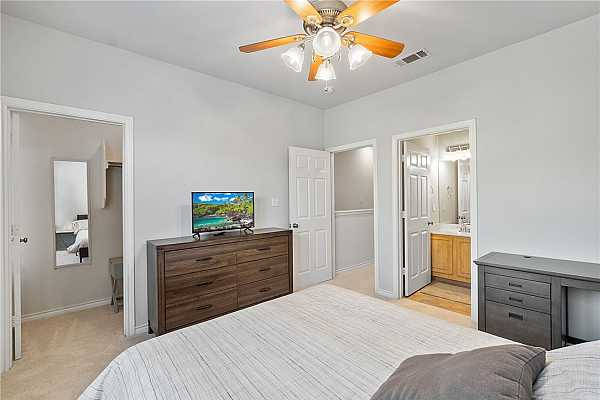 Photo #11 The first primary suite features plush carpet flooring, a ceiling fan, a walk-in closet, and an en-suite.