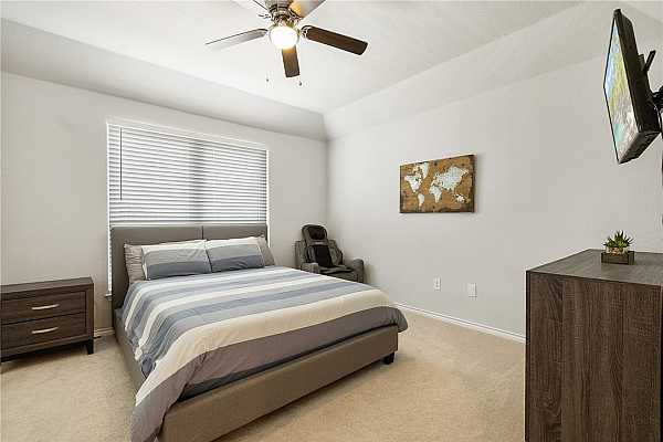 Photo #13 The second primary suite features plush carpet flooring and a vaulted ceiling with a ceiling fan.