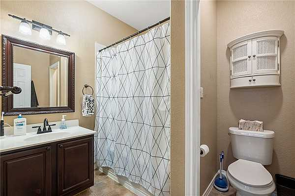 Photo #15 The second en-suite is equipped with a single vanity, a decorative framed mirror, a water closet, and a soaking tub/shower combo.