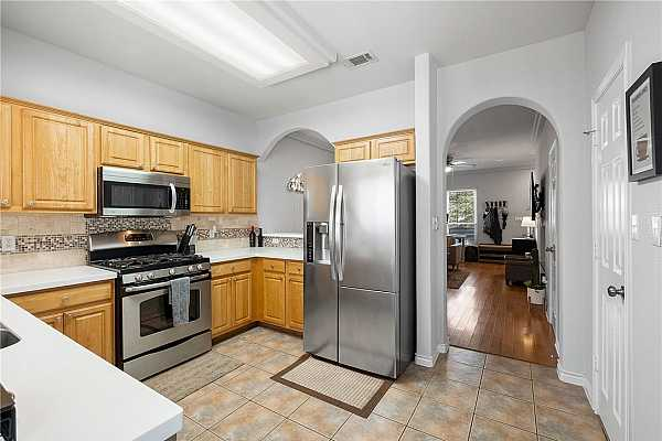 Photo #7 The kitchen offers a functional design with sleek quartz countertops and beautiful tile backsplash with mosaic detailing.
