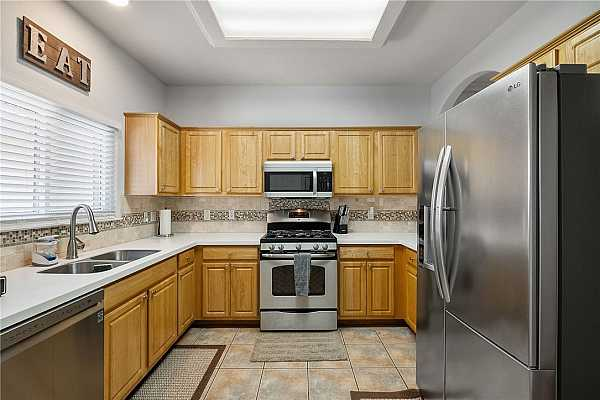 Photo #8 The kitchen is equipped with quality stainless steel appliances including a gas range and refrigerator that convey with the home.