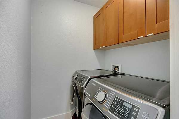 Photo #13 Full size washer/dryer will convey. Cabinets above the washer/dryer offer more storage solutions!