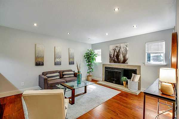 Photo #2 Spacious living room features a fireplace, acacia wood floors, and designer paint.