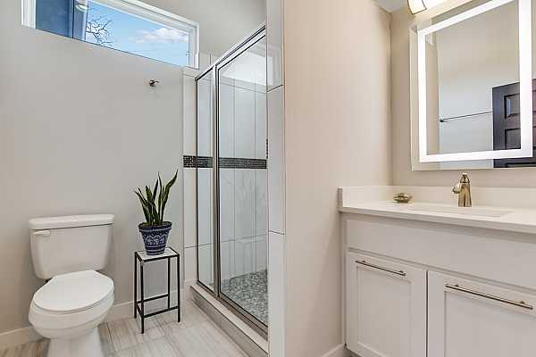 Photo #18 The guest bathroom features a single vanity, ample storage space, and a walk-in shower.