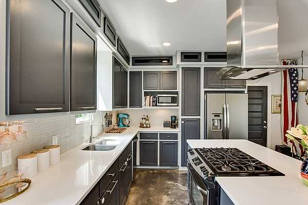 Photo #5 The kitchen is bound to impress any home chef and features modern quartz countertops, painted shaker-style cabinetry with stainless-steel hardware, and upscale stainless-steel appliances including a freestanding gas range.