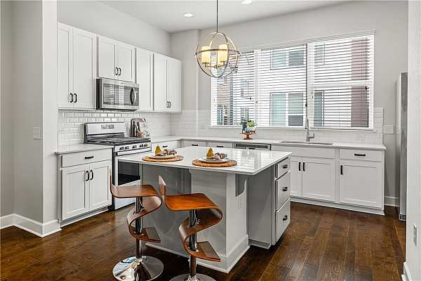 Photo #21 Kitchen island features a breakfast bar for your morning cereal.